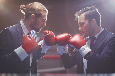 Two competitive businessmen in suits and boxing gloves attacking one another photo
