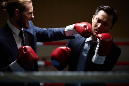 Gloating businessman fighting with rival photo