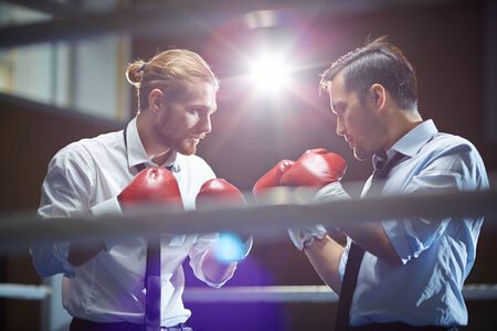 Serious businessmen in boxing gloves attacking one another in gym or boxing ring photo