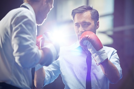 Serious businessman in boxing gloves looking at his rival before attack photo