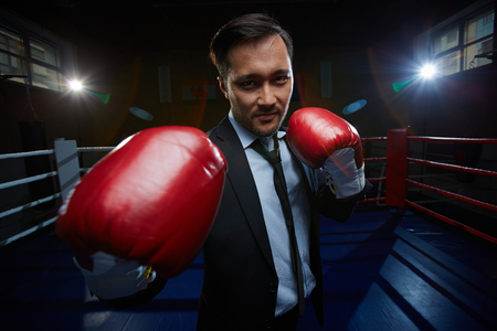 business rival: Strong and confident businessmen in suit and boxing gloves looking at camera