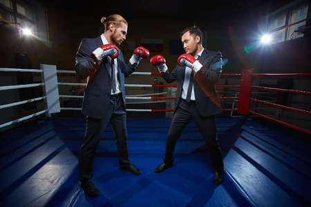 Professional businessmen in suits and boxing gloves standing opposite one another on boxing ring photo