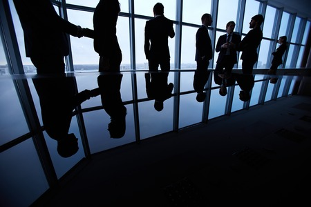 Group of business people standing against office in board room and interacting Stock Photo