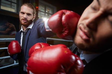rival: Aggressive businessman hitting his rival Stock Photo