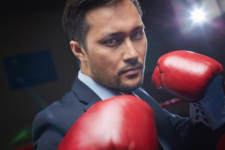 Asian businessman in red boxing gloves looking at camera photo