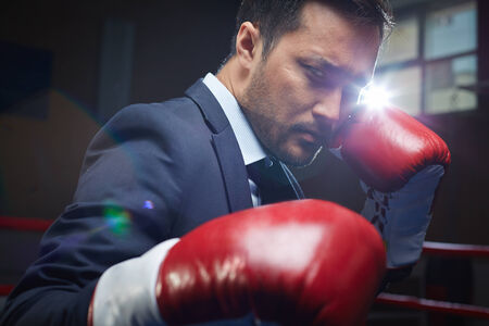 Asian businessman wearing red boxing gloves photo