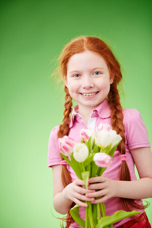 Adorable girl with bunch of tulips over green background photo