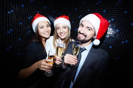 Groep van vrolijke mensen uit het bedrijfsleven in Santa caps roosteren met champagne in nachtclub