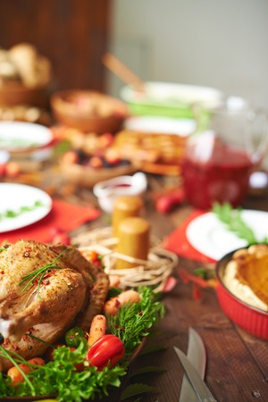 Roasted turkey with pepper, carrots and greenery on festive table photo