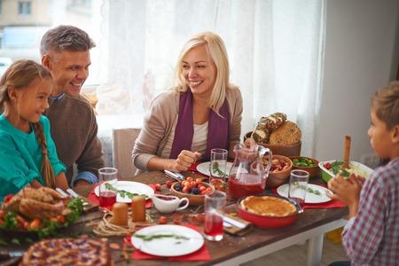 cena navideña: Familia de cuatro miembros feliz que celebra el día de Acción de Gracias