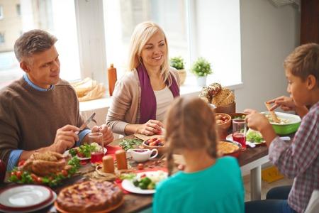 Familia feliz de cuatro comer comida tradicional de Acción de Gracias por la tabla