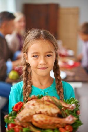 familia cristiana: Retrato de niña linda con las aves de corral cocido mirando a la cámara con su familia en el fondo