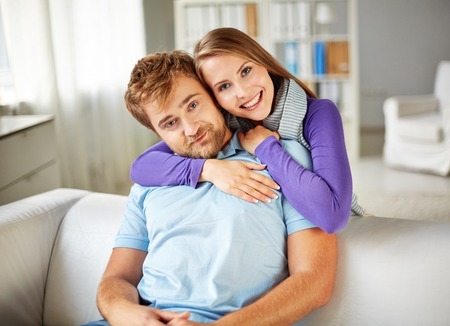 restful: Restful young couple looking at camera while spending weekend at home Stock Photo