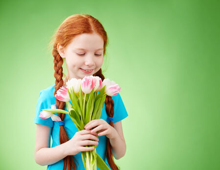 Adorable girl looking at bunch of tulips in her hands photo