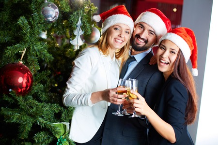 company party: Friendly co-workers in Santa caps toasting with champagne by Christmas tree in office