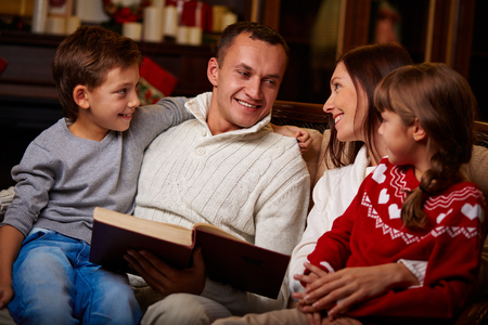 Portrait of happy family reading book on Christmas evening at home photo