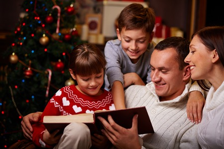 familhia: Família moderna de quatro lendo contos de fadas de Natal Banco de Imagens