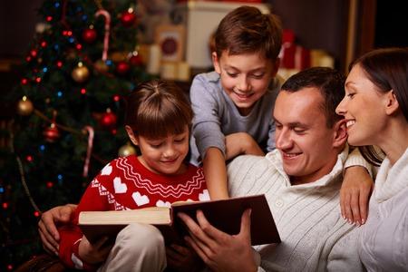 ni�os felices: Familia moderna de cuatro que leen los cuentos de hadas de Navidad