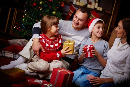 Portrait of friendly family with gifts spending Christmas evening at home photo