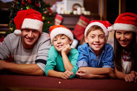 Christmas family in Santa caps looking at camera at home photo
