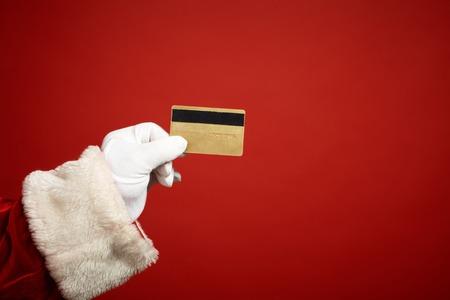 プラスチック製のカードを持っているサンタ クロースの手袋をはめた手