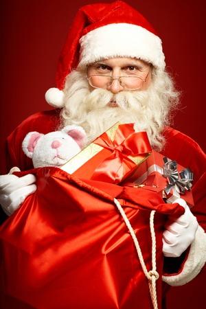 generoso: Generoso Pap� Noel que sostiene gran saco rojo con giftboxes y juguetes Foto de archivo