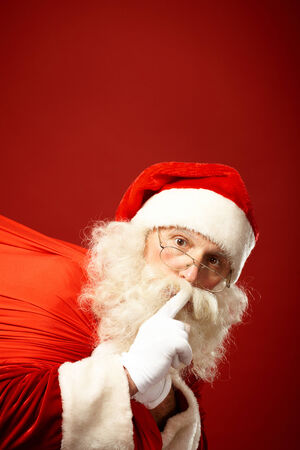Portrait of Santa Claus carrying sack and keeping forefinger by his mouth photo