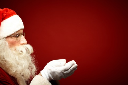 Santa Claus in eyeglasses holding snow on his palms Stok Fotoğraf