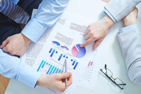 revisando documentos: Primer plano de las manos femeninas y masculinas que señalan en el documento de negocio con diagramas y gráficos Foto de archivo