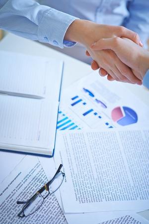 manos unidas: Los socios comerciales Apret�n de manos sobre el lugar de trabajo con documentos de negocios Foto de archivo