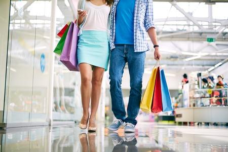 go shopping: Legs of young couple shopping in trade center