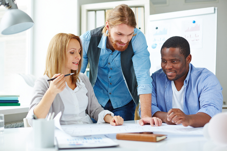 Multi-ethnic employees looking at blueprint while explaining its features photo