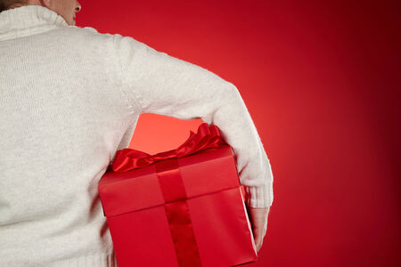 Man in white sweater holding big red giftbox in isolation photo