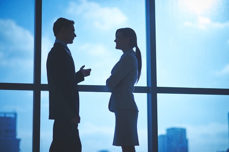 Contornos de socios de negocios hablando por la ventana en la oficina