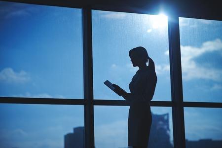 siluetas mujeres: Esquema de la empresaria con la creaci�n de redes touchpad junto a la ventana en la oficina