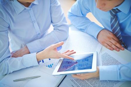 会議でタッチパッドでビジネス ドキュメントを議論する 2 人の従業員 写真素材