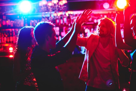 nightclub crowd: Group of happy friends dancing in nightclub