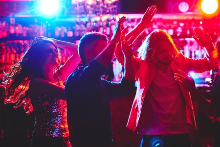 nightclub crowd: Group of young people with raised arms dancing in nightclub