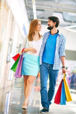 shopaholism: Happy young couple in casual during shopping in the mall Stock Photo