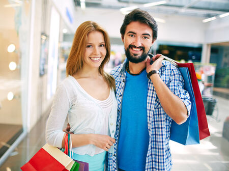 Portrait of young couple with paperbags looking at camera after shopping photo