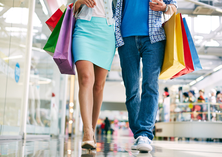 go inside: Legs of young couple with paperbags going in the mall