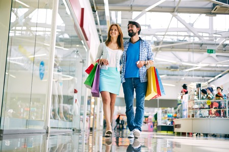 go inside: Casual couple walking in the big mall