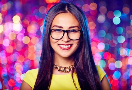 Asian female in eyeglasses looking at camera at party 版權商用圖片