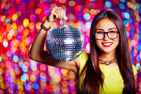 Portrait of glamorous Asian girl with sparkling disco ball looking at camera photo