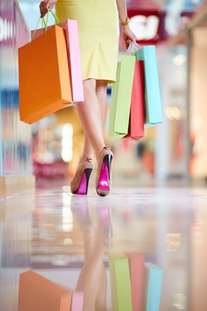 Rear view of elegant shopaholic with shopping bags leaving the mall photo