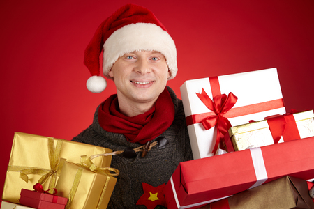 Portrait of happy man in Santa cap holding packed gifts photo