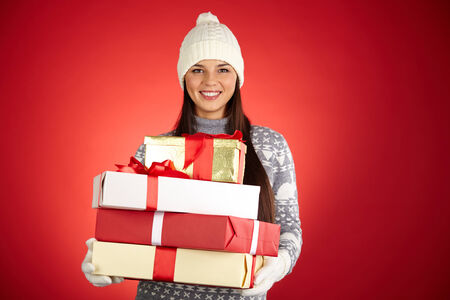 winterwear: Portrait of happy girl in winterwear holding stack of giftboxes over red background