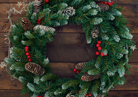 Christmas conifer wreath with firtree cones, red berries and garlands photo