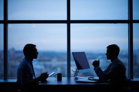 trabajando: Contornos de dos hombres de negocios trabajando hasta tarde en la oficina
