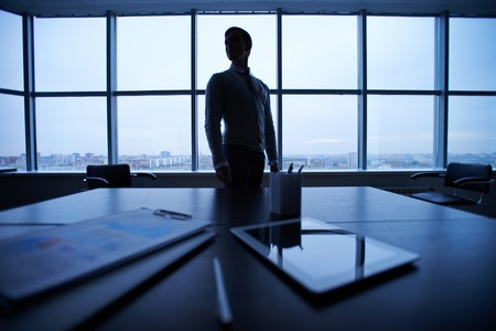 Business documents and touchpad at workplace on background of man by the window photo